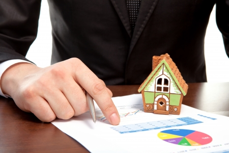 businessman sitting at the table with charts and a house and sign a contract photo