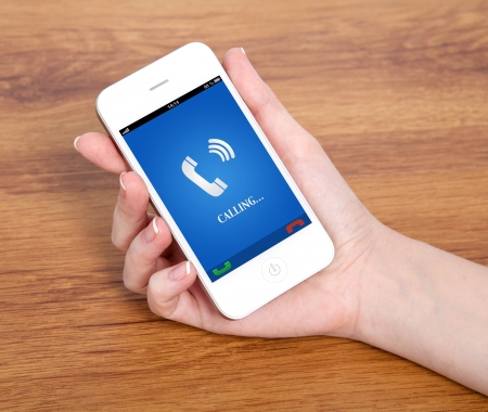 woman hand holding a touch phone with blue screen and the phone ringing tube against the background of a wooden table