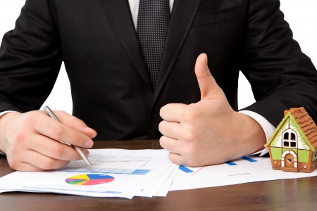 businessman sitting at the table with charts and a house and sign a contract Stock Photo