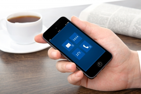 businessman hand holding a phone with interface on a screen against the background of the table in the office