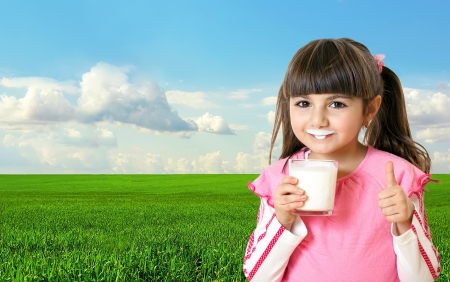 field glass: Beautiful little girl holding a glass of milk and smiling in the background of green field and blue sky Stock Photo