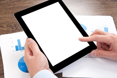 businessman holding a tablet computer with isolated screen on the table with graphics photo