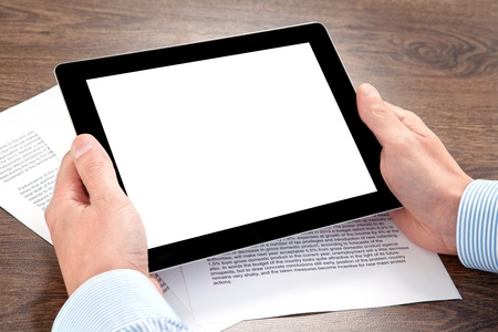 businessman holding a tablet computer with isolated screen on the table with documents photo