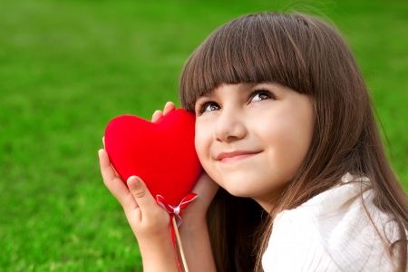 beautiful little girl lying on green grass and holding a red heart photo
