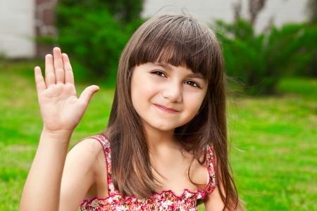 mooi meisje zwaait met haar hand op een achtergrond van groen gras