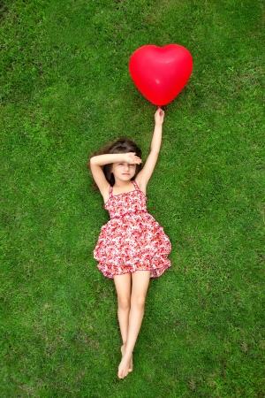 草の上に横たわると、心臓の形に赤いボールを保持している色のドレスで美しい少女