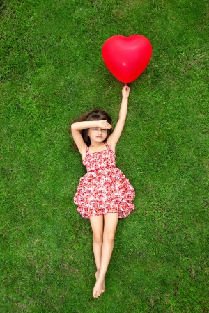 to lie: beautiful girl in color dress lying on the grass and holding a red ball in the form of heart