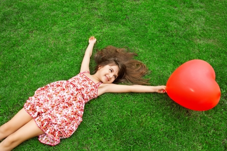 child s: beautiful girl in color dress lying on the grass and holding a red ball in the form of heart