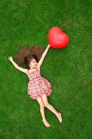 niña: hermosa chica en traje de color tumbado en la hierba y la celebraci?e una bola roja en forma de coraz?