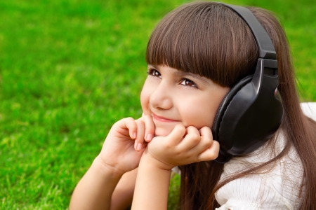 beautiful little girl lying on green grass with headphones and listening to music photo