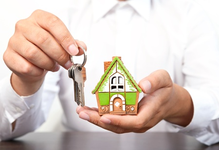 house exchange: businessman in white shirt holding a small house and apartment keys in hand