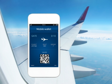 white phone with mobile wallet and plane ticket against the background of the window with blue sky and airplane wing photo