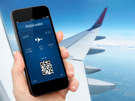 airplane window: woman hand holding the phone with mobile wallet and plane ticket against the background of the window with blue sky and airplane wing