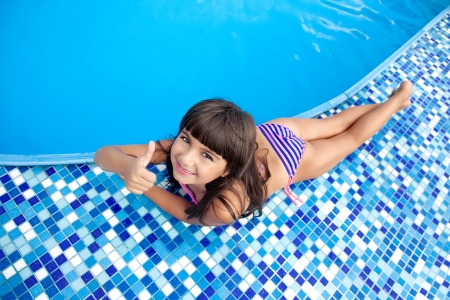 beautiful little girl in a bathing suit lies near the blue pool and shows the hand cool Stock Photo