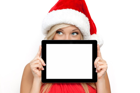 christmas display: blonde girl in a red Christmas hat on New Year, holding tablet computer touch pad gadget with isolated screen