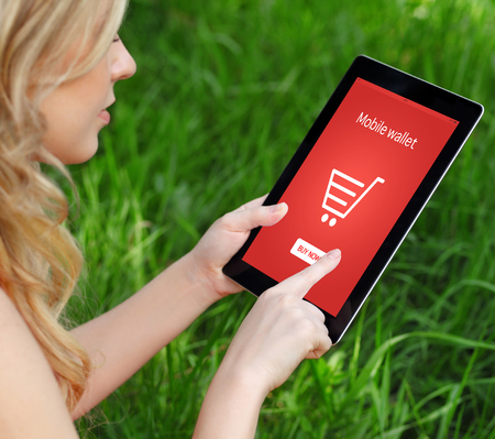 girl holds a tablet on a background of green grass and makes online shopping photo