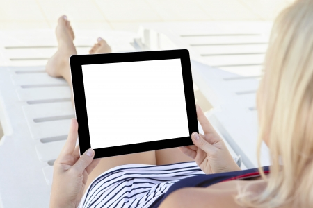 girl in a bathing suit lying on a white chaise lounge with a computer tablet with isolated screen Stock Photo