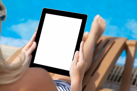 girl in a bathing suit lying on a sun lounger by the pool with a computer tablet with isolated screen