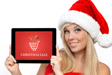 blonde girl in a red Christmas hat on New Year, holding tablet computer with christmas sale on a screen photo
