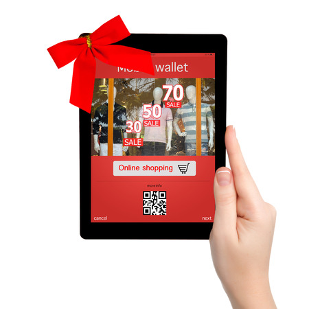 female hand holding a tablet with red gift bow and mobile wallet onlain shopping on the screen photo