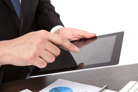businessman holding a tablet computer on the table with graphics photo