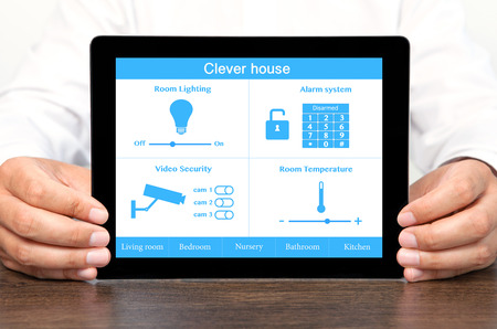 businessman holding a tablet computer with system clever house photo