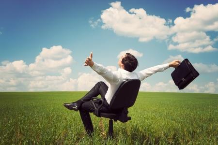 contrato de trabajo: hombre de negocios en un traje en un campo verde con un cielo azul, sentado en una silla de oficina y agitando los brazos Foto de archivo