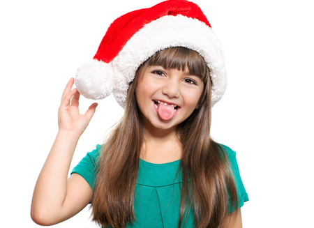 Isolated portrait of a little girl in a Christmas hat that shows the tongue photo