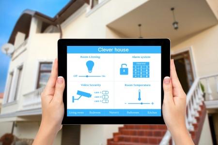 여성의 손은 집안의 배경에 화면에 시스템 영리 하우스와 함께 태블릿 컴퓨터를 잡아