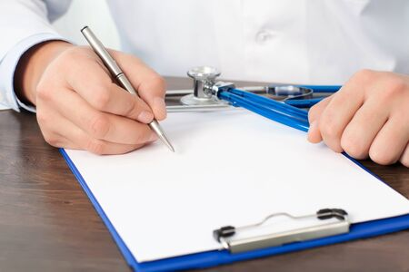 doctor writing: Doctor sitting at his desk with a stethoscope and writing something on a white sheet Stock Photo