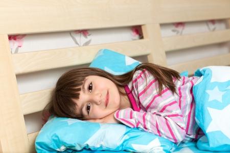 pijama: hermosa niña en el sueño pijama en la cama bajo una manta azul Foto de archivo