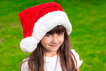 portrait of a pretty little girl in a Christmas hat on a background of green grass photo