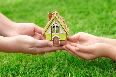 hands holding house: Hands mother and a small child holding a little toy house on a background of green grass