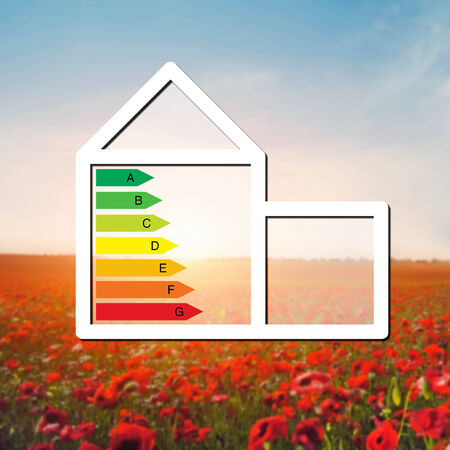 house with the sign of energy saving on a background field with red flowers photo