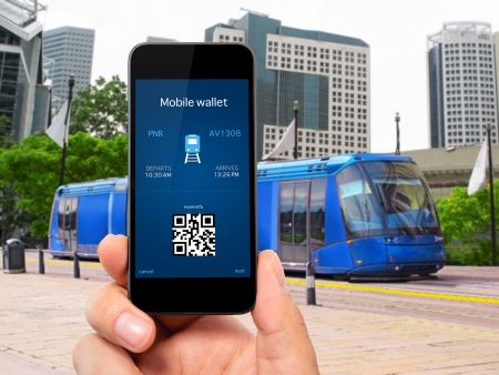 train ticket: man hand holding the phone touch with a mobile wallet and train ticket against the blue train to the city
