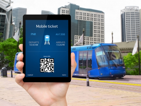 train ticket: man hand holding the tablet with a mobile wallet and train ticket against the blue train in the city Stock Photo