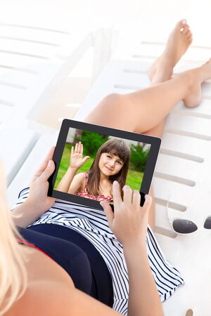 woman in a bathing suit lying on a chaise lounge with a computer tablet and communicates by video voice chat with a young child Stock Photo - 25488014