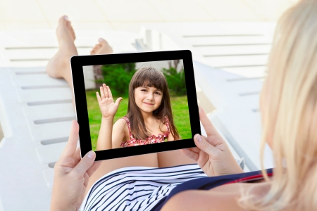 woman in a bathing suit lying on a chaise lounge with a computer tablet and communicates by video voice chat with a young child photo