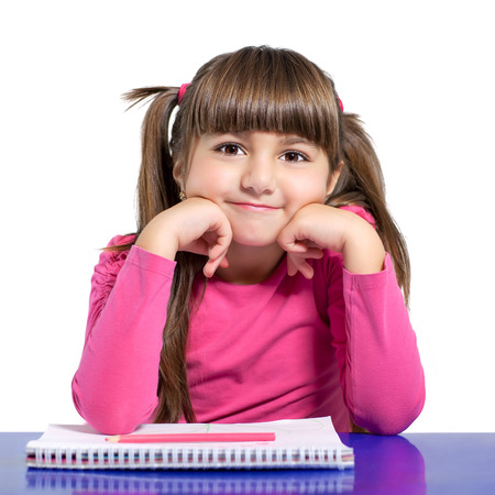 isolated little girl in a pink shirt is sitting at the table with colored pencils  photo
