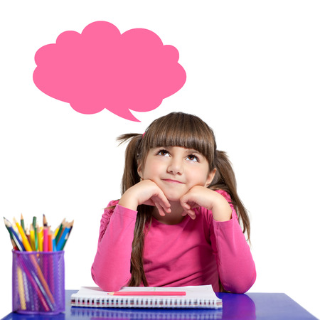 isolated little girl in a pink shirt is sitting at the table with colored pencils and looks at the cloud for thought photo