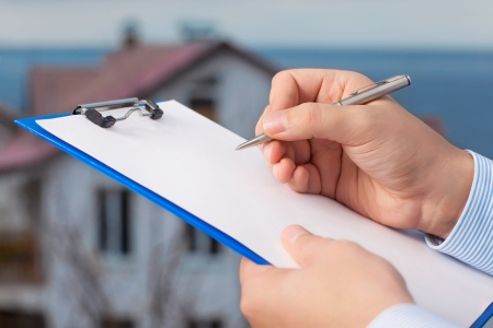 building insurance: businessman signs a document on the background of an apartment building with blue sky Stock Photo