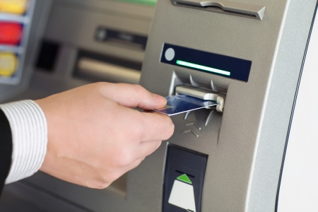 male hand businessman inserts credit card into the ATM and withdraws money photo