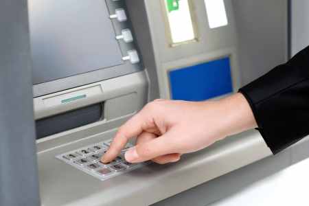 man enters a PIN code and withdraws money from an ATM photo