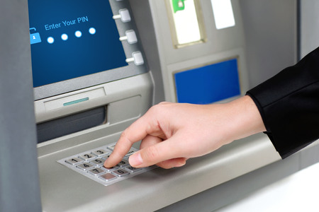 man enters a PIN code and withdraws money from an ATM Stock Photo