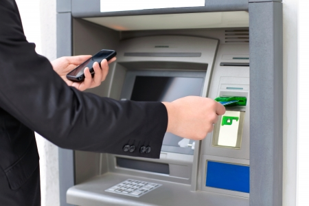businessman inserts a credit card into the ATM to withdraw money and holding a phone photo