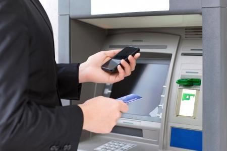 zakenman staande in de buurt van de ATM en met een creditcard en mobiele telefoon in handen
