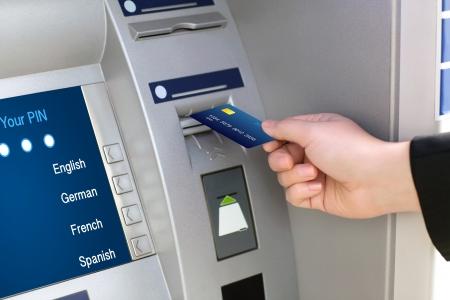 hombre de negocios hombres mano pone la tarjeta de crédito en cajeros automáticos Foto de archivo