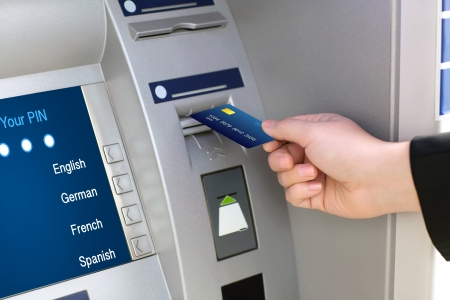 machines: men hand businessman puts credit card into ATM