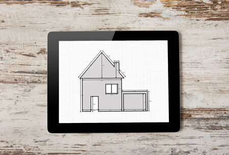 Tablet computer with drawing of apartment house on the screen on a background of wood