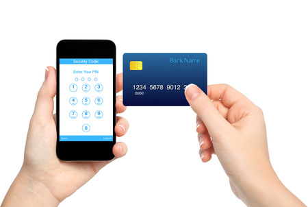 pin code: isolated female hands holding phone and credit card and enter a PIN code  Stock Photo